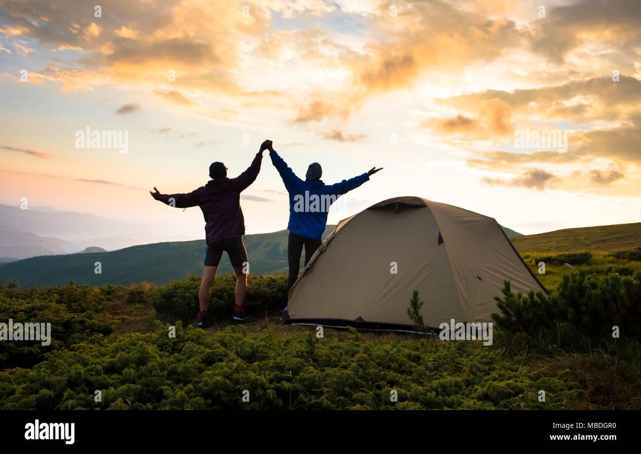 Il campeggio e il giovane sulla sommità di alta montagna Immagini Stock