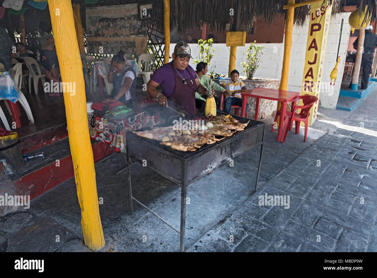 Uomo al chicken grill sul ciglio della strada in pista, Yucatan, Messico Immagini Stock