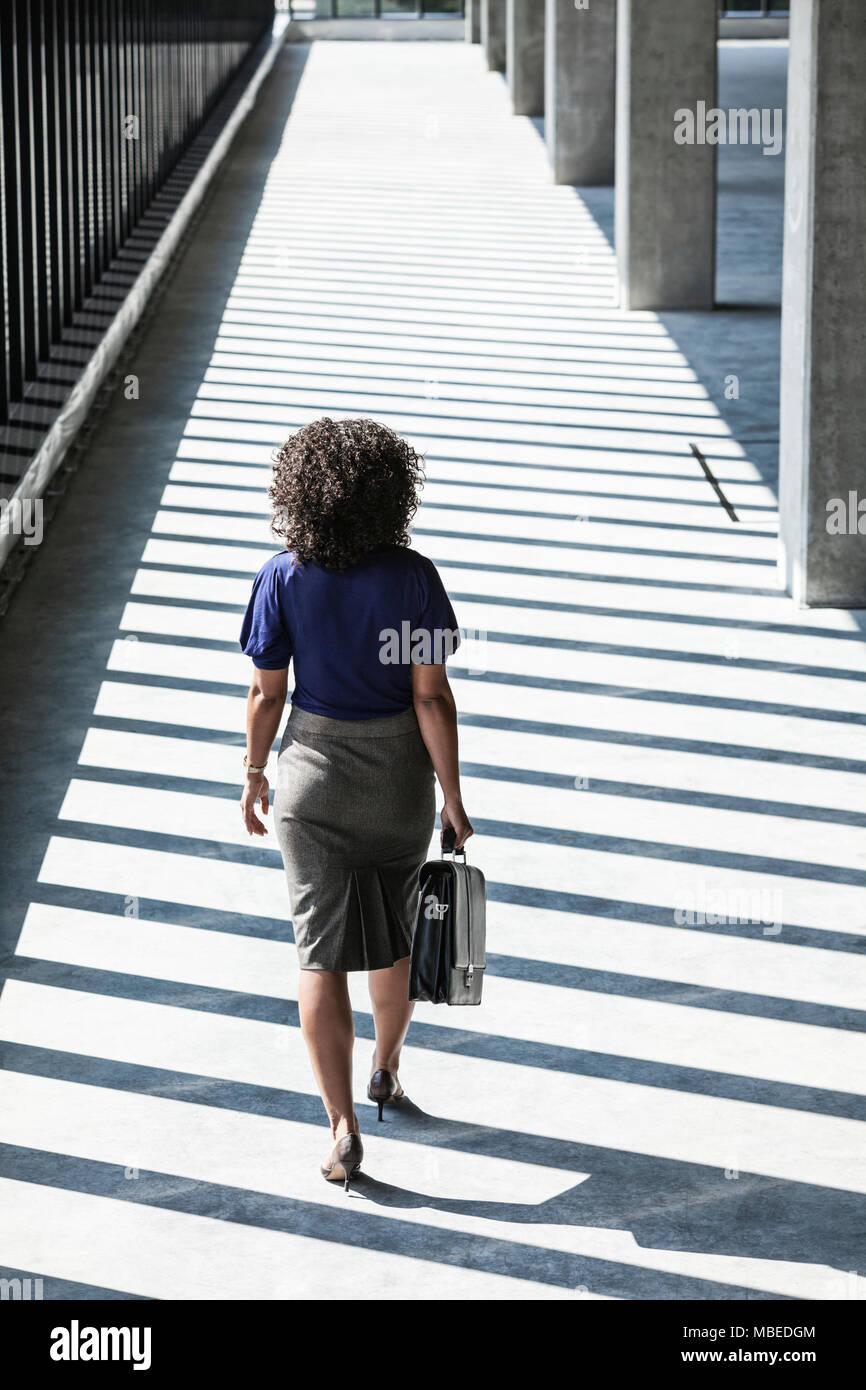 Imprenditrice a piedi attraverso grandi vuoti di spazio ufficio illuminata dal sole del pomeriggio. Immagini Stock