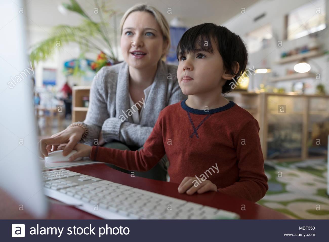 Insegnante di scuola materna e ragazzo studente al computer Immagini Stock