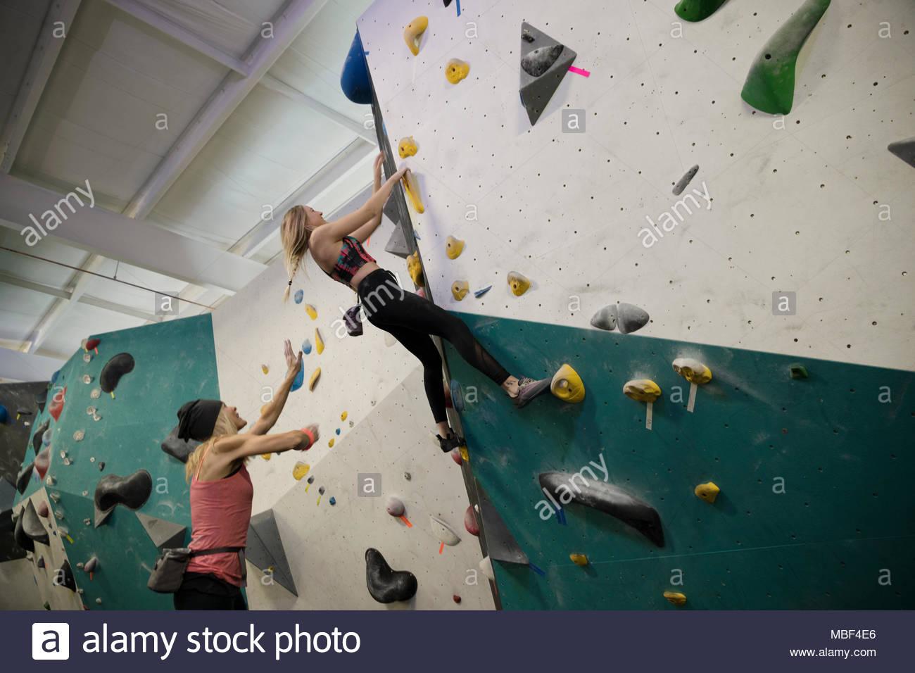 Femmina di rocciatore spotting partner parete di arrampicata in palestra di arrampicata Immagini Stock