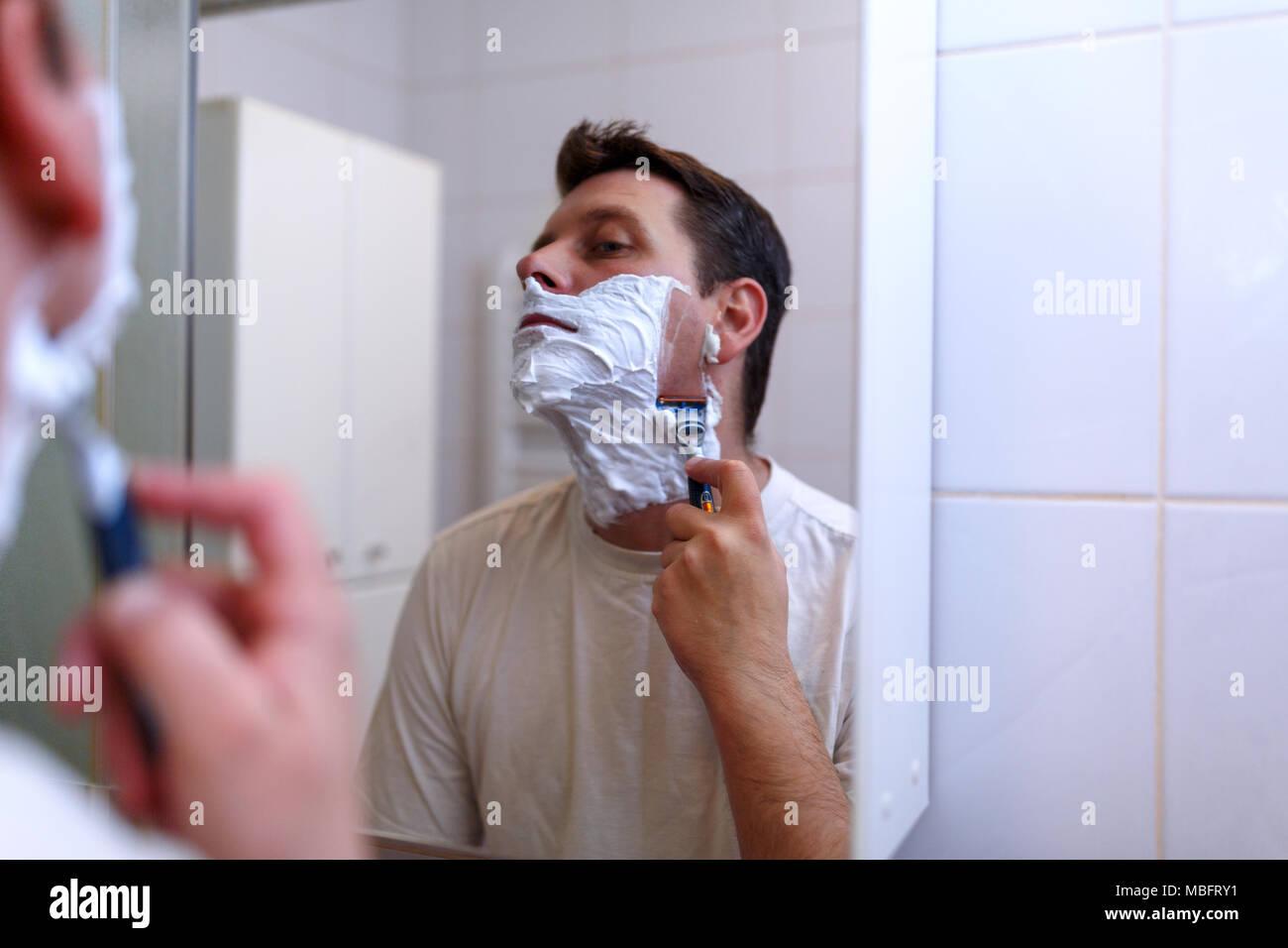 Giovane uomo la rasatura con il rasoio e crema di rasatura nella stanza da bagno Immagini Stock