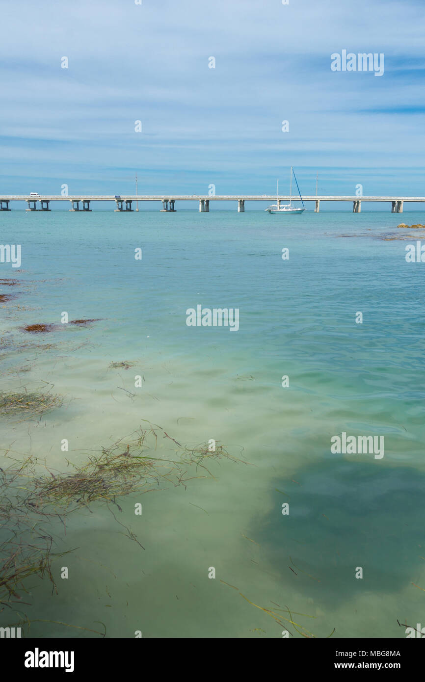 Stati Uniti d'America, Florida, Overseas Highway bridge con barca a vela in acqua chiara Immagini Stock