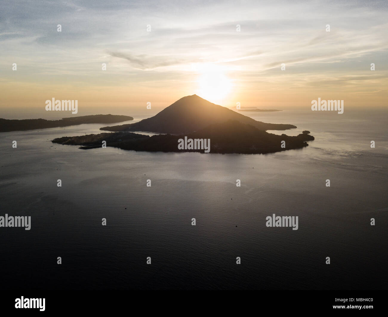 Il sole tramonta dietro Banda Neira, un vulcano attivo nella banda del mare. Questa regione è nel triangolo di corallo e presenta una elevata biodiversità marina. Immagini Stock