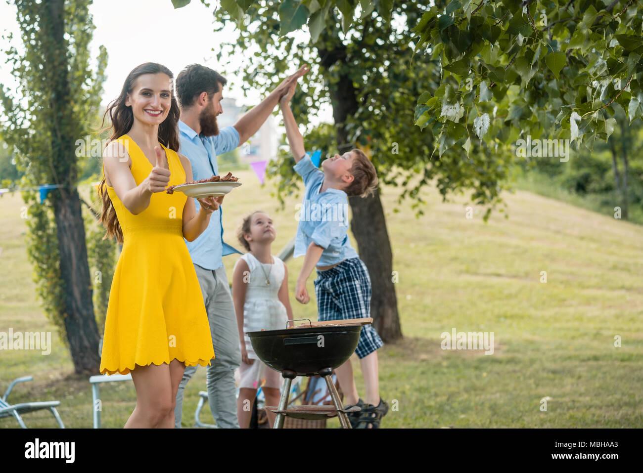Madre bella mostra pollice in alto mentre il trascorrere del tempo di qualità con la famiglia Immagini Stock
