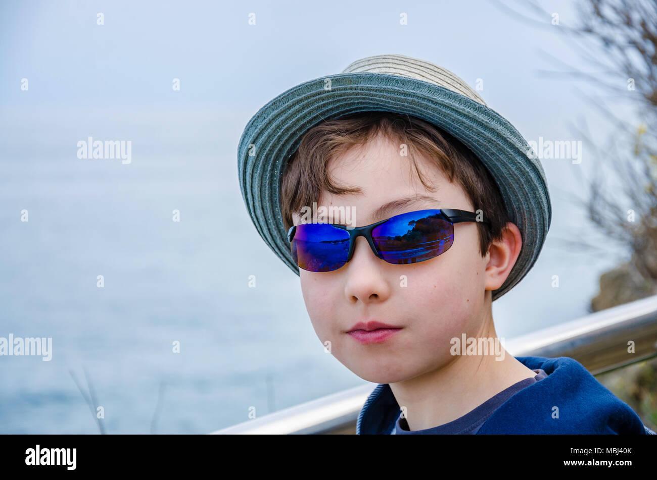 Un ritratto di un 8 anno vecchio ragazzo che indossa gli occhiali da sole e un  cappello per il sole. f38621012c2d