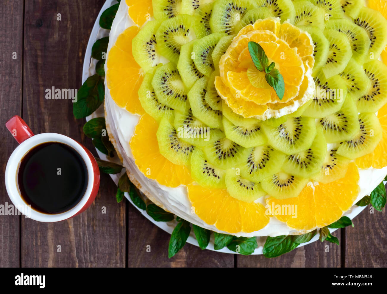 Brillante Rotondo frutta festosa torta decorata con kiwi, arancio, menta e una tazza di caffè. Immagini Stock