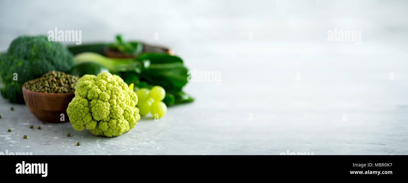 Verde biologico di frutta e verdura su sfondo grigio. Spazio di copia, piatto di laici che, vista dall'alto. Verde mela, avocado, kale, calce, kiwi, uva, broccoli, in marmo di lenticchie, Mung bean. Banner Immagini Stock