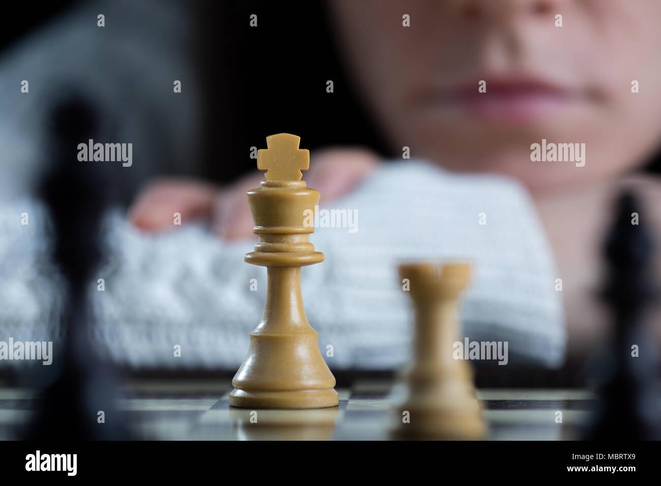 Grave donna giocando a scacchi a guardare la scacchiera Immagini Stock