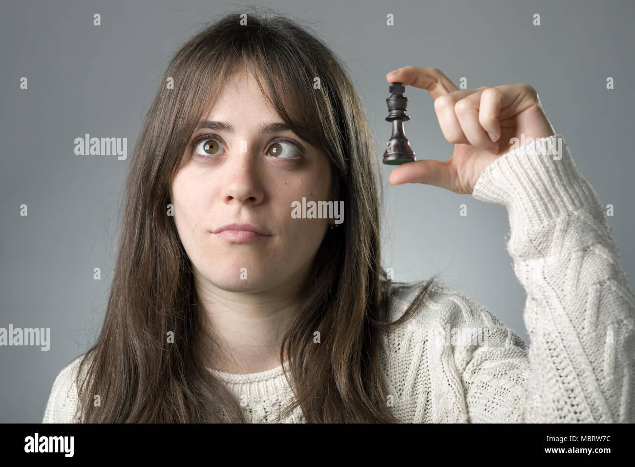 Socchiudendo gli occhi donna tenendo un re pezzi di scacchi Immagini Stock