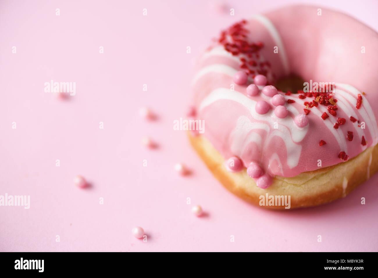 Dolce ciambella con glassa rosa su sfondo color pastello. Una gustosa ciambella sulla texture rosa, copia spazio, vista dall'alto Immagini Stock