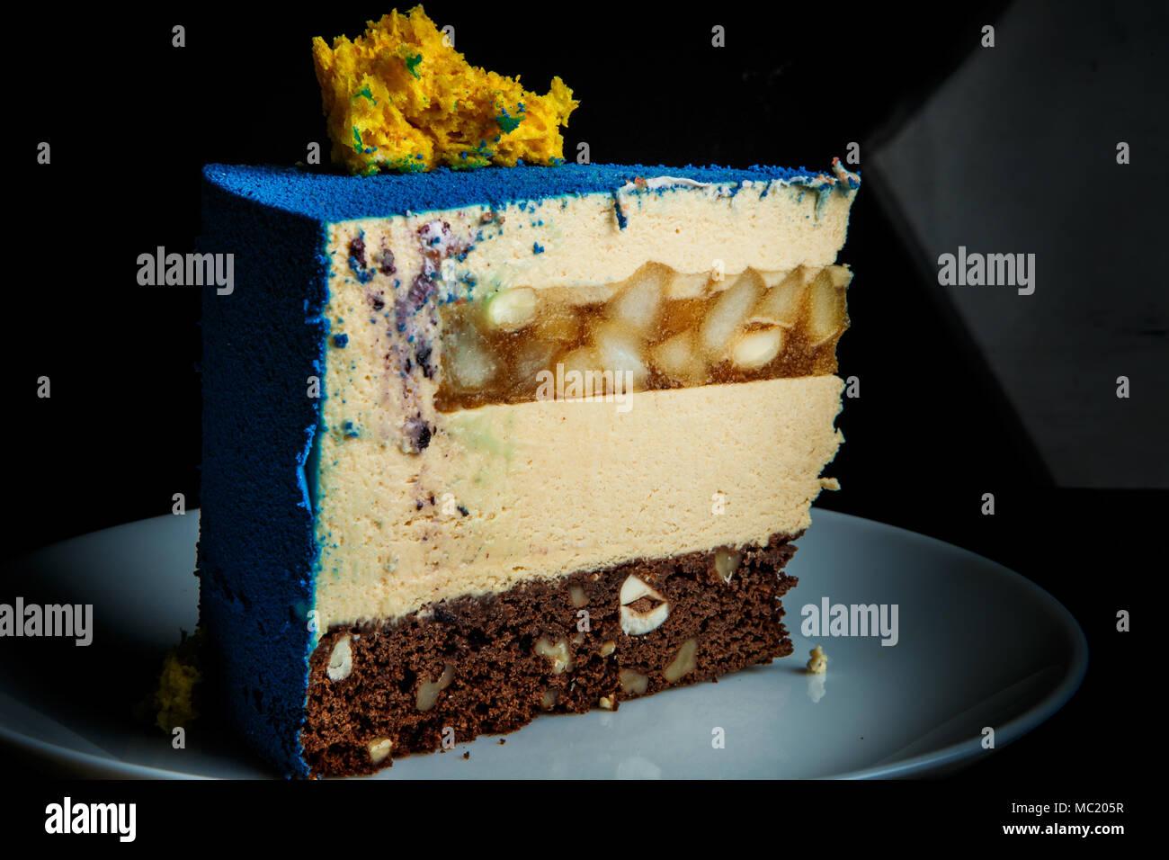 Closeup pezzo di mousse di blu la torta con la spugna gialla decorazione  torta sulla parte superiore e caramello pera strato inter sorge sulla  piastra