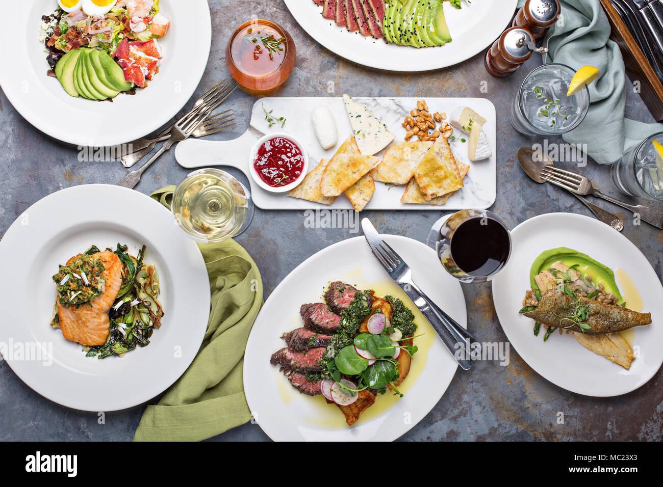 Grande tavola di cena vista aerea con bistecche e pesce Immagini Stock