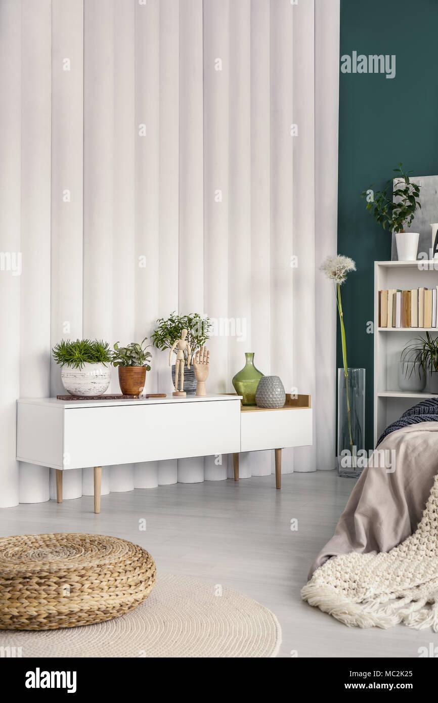 Pouf vicino al bianco credenza con piante in camera da letto moderno ...