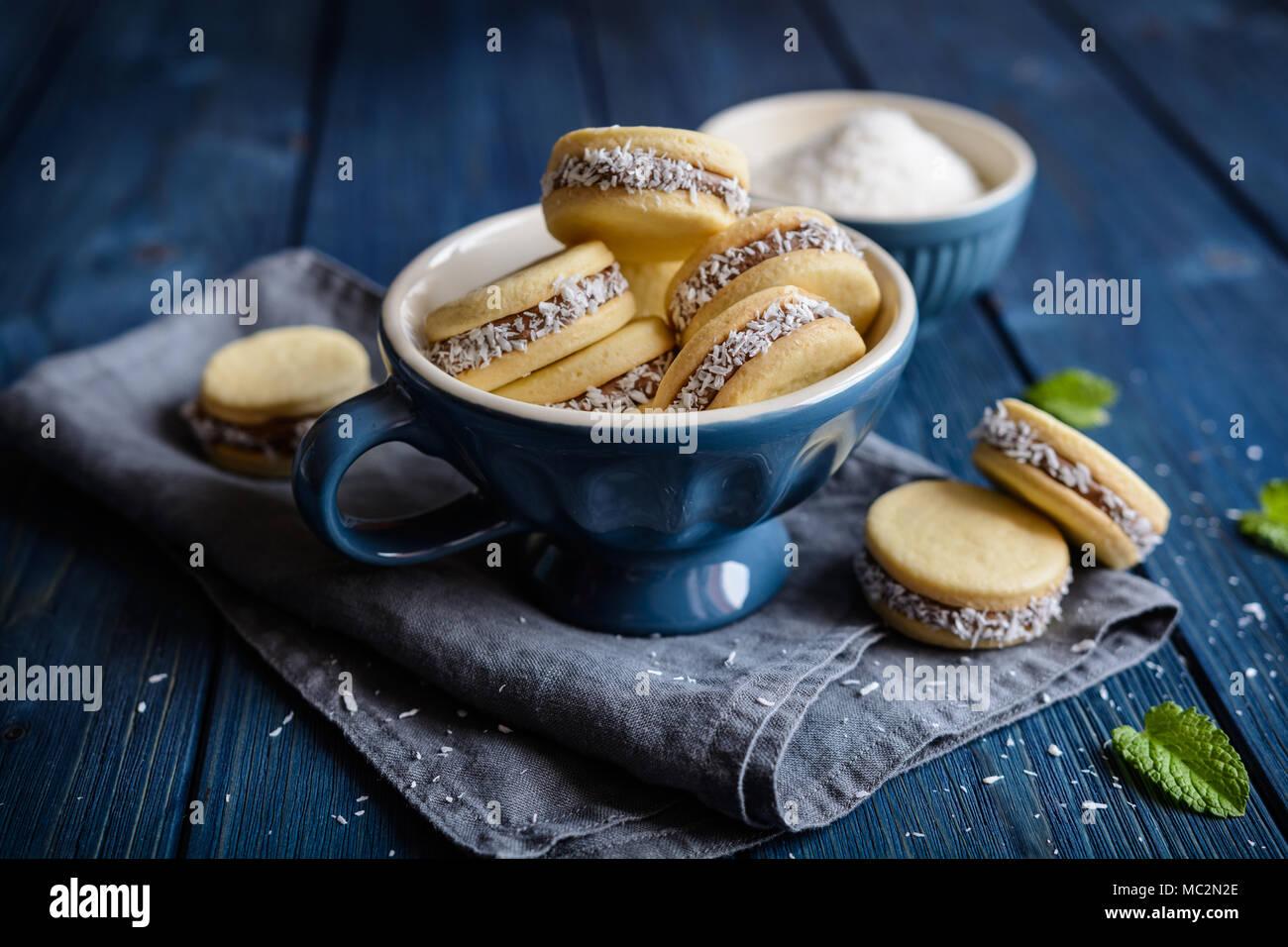 Alfajores - tradizionale panino cookie riempito di latte caramellato e noce di cocco Immagini Stock