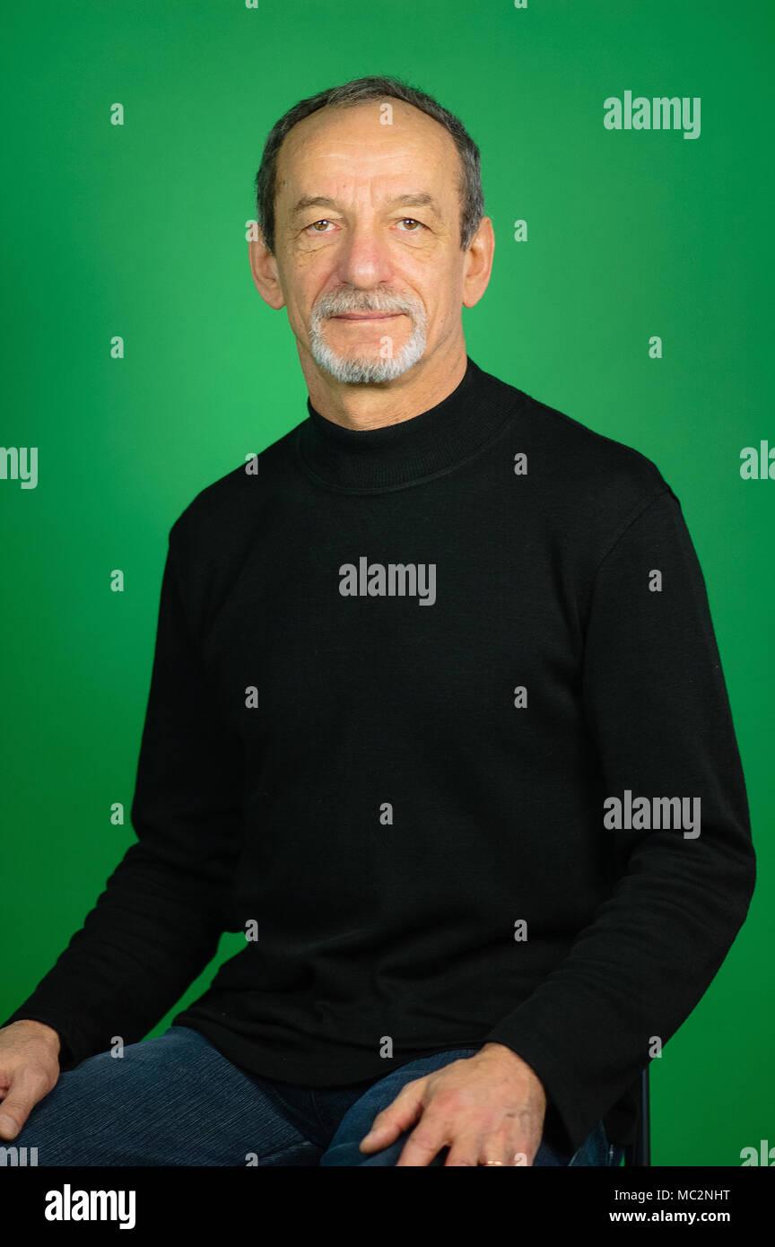 Ritratto di un uomo maturo su uno sfondo verde. Maglione nero benevola  espressione facciale a012807fc3c8