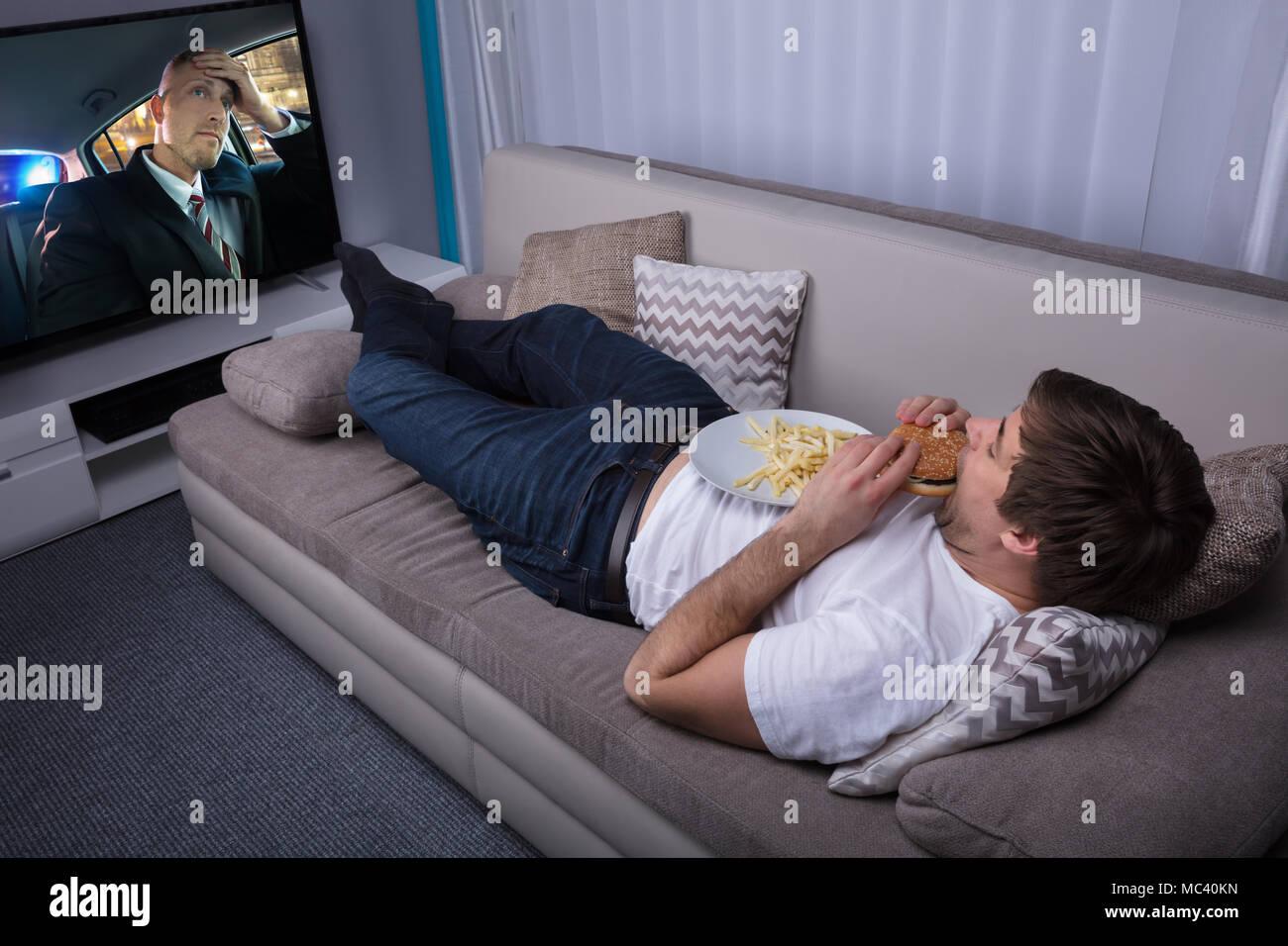 Giovane Uomo sdraiato sul divano a mangiare patatine fritte e Burger Immagini Stock