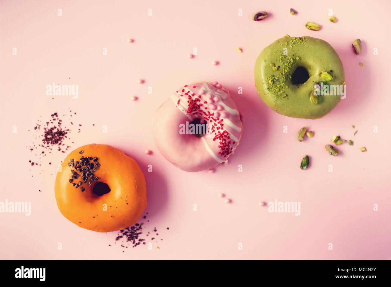 Ciambelle Colorate Con Ciliegina Sulla Rosa Pastello Sfondo Arancio