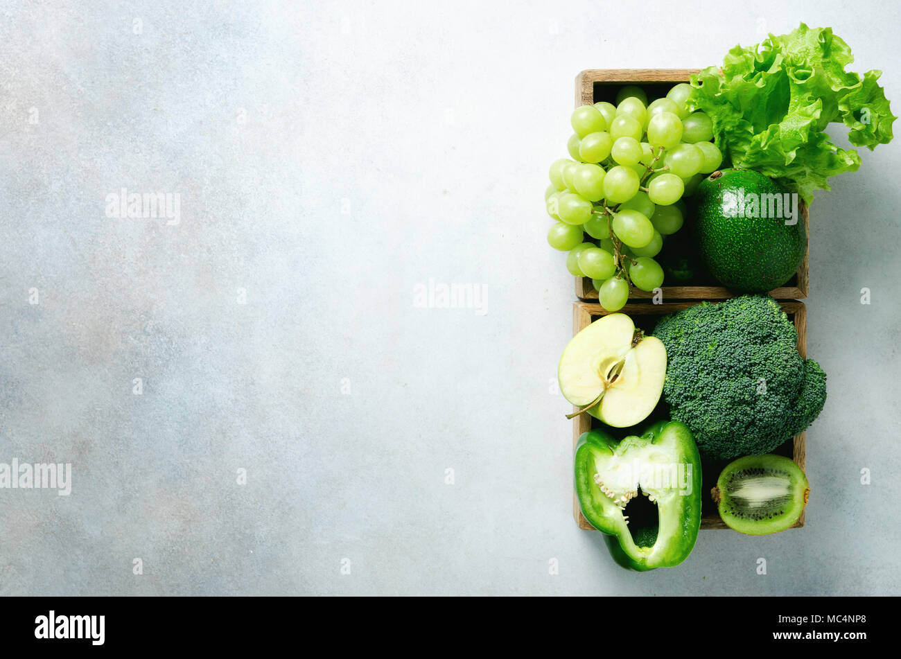 Verde biologico di frutta e verdura su sfondo grigio. Spazio di copia, piatto di laici che, vista dall'alto. Verde mela, lattuga, zucchini, cetrioli, avocado, kale, calce, kiwi, uva, banana, broccoli Immagini Stock