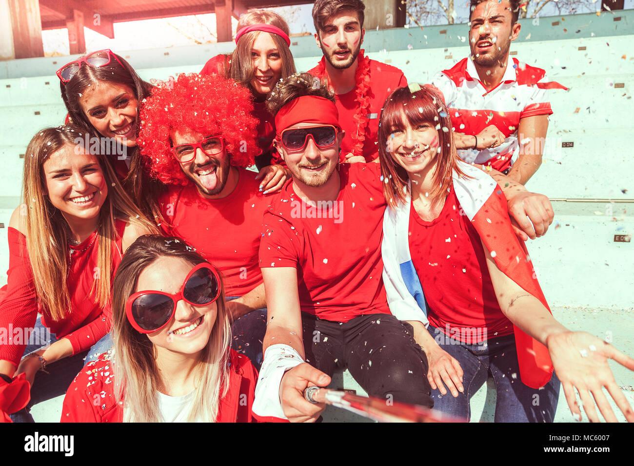 Gruppo di fan vestiti di rosso il colore prende un selfie nelle gabbie di  uno stadio durante un evento di sport 11ad3d532a3