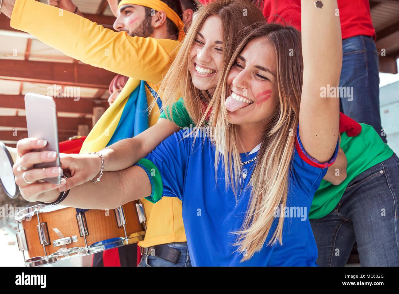 Due felice bella ragazza bionda prende un selfie nelle gabbie di uno stadio  durante un evento 83dc48f14b9