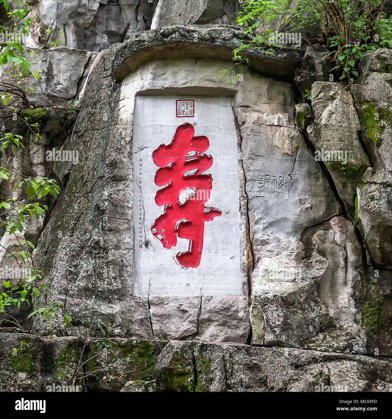 Un iscrizione e la scultura in pietra alla base della Vetta della Bellezza Solitaria, Guilin, Cina. Il dipinto di rosso il carattere cinese è Shou, il che significa che la longevità. Immagini Stock