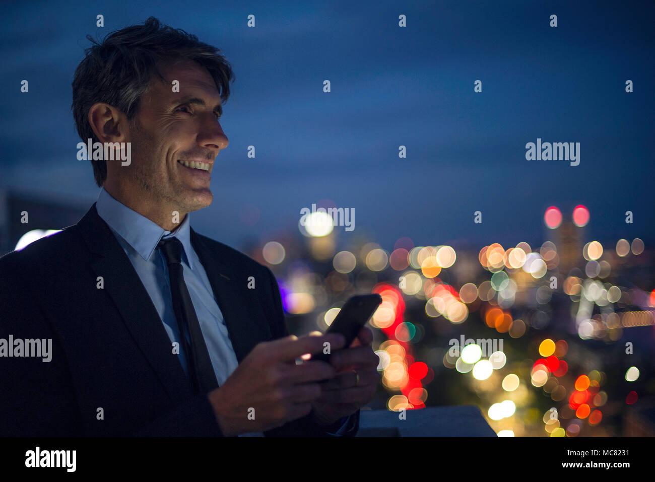 Imprenditore su alto tetto utilizzando il telefono cellulare Immagini Stock