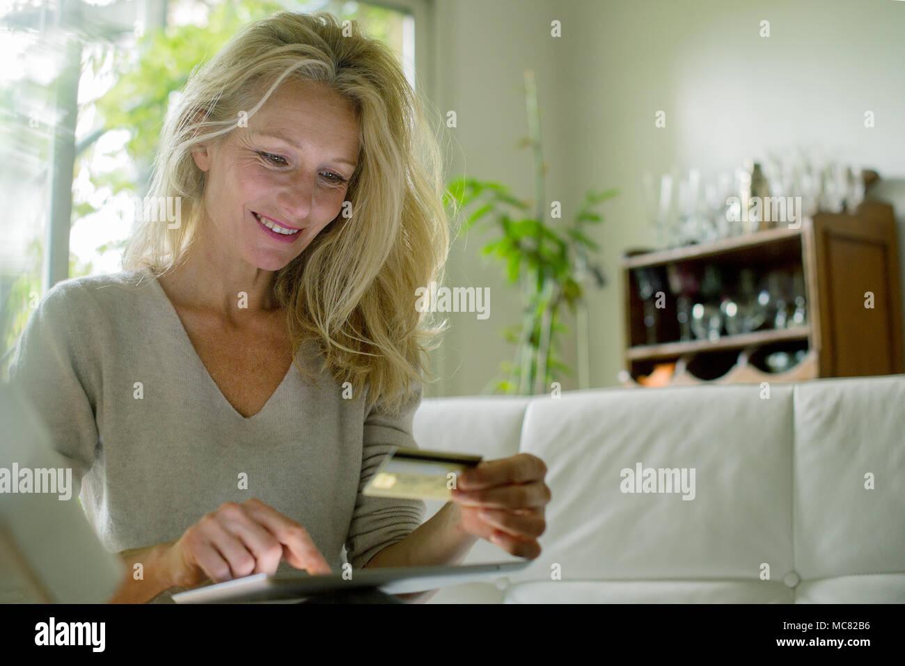 Donna matura utilizzando il tavolo digitale per shop online Immagini Stock