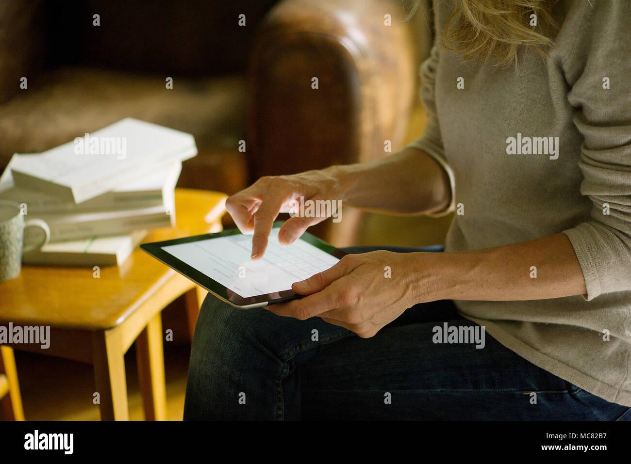 Donna con tavoletta digitale in casa Immagini Stock