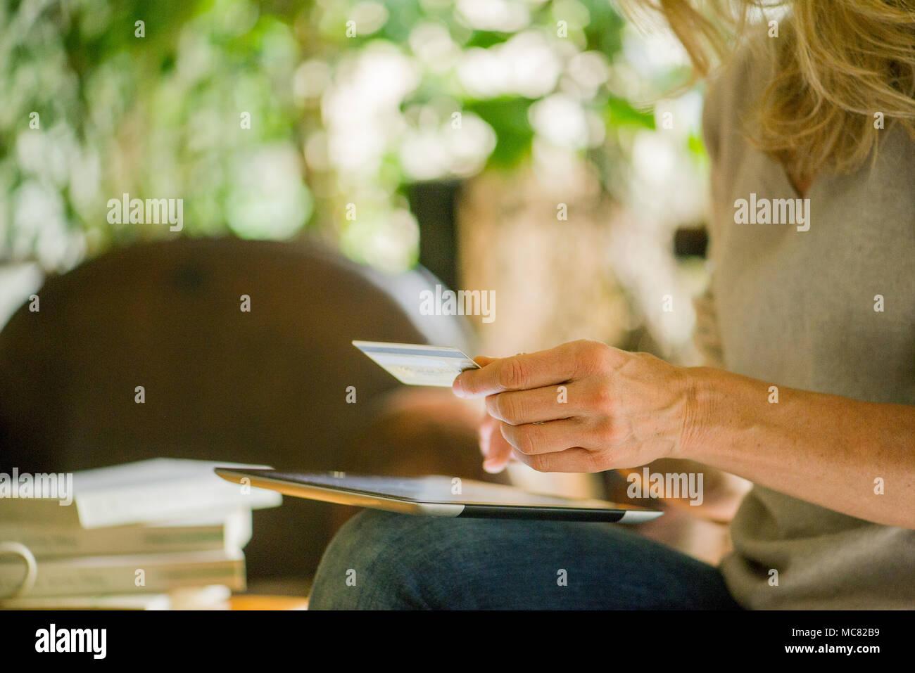 Donna con tavoletta digitale e una carta di credito, ritagliato Immagini Stock