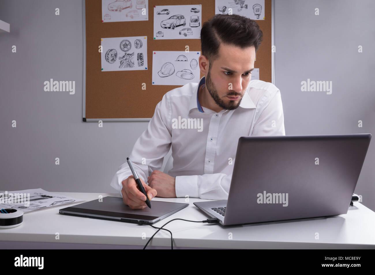 Designer maschio con tavoletta grafica lavorando sul computer portatile Immagini Stock