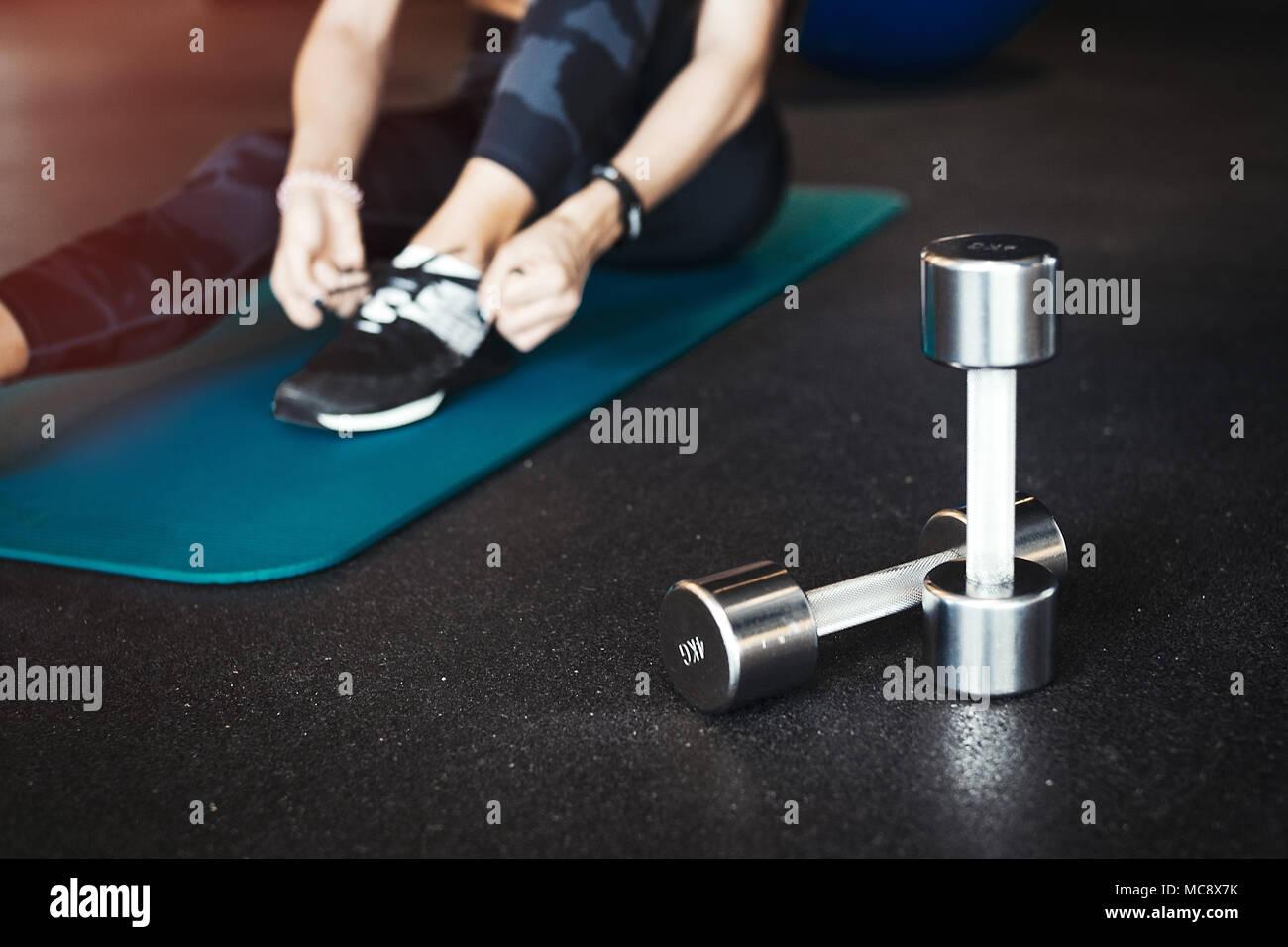 Giovane attraente ragazza bruna enlacing il suo sport calzature dopo la pratica di allenamento e formazione crossfit su blu materassino yoga. Donna sfocata è su backgroun Immagini Stock