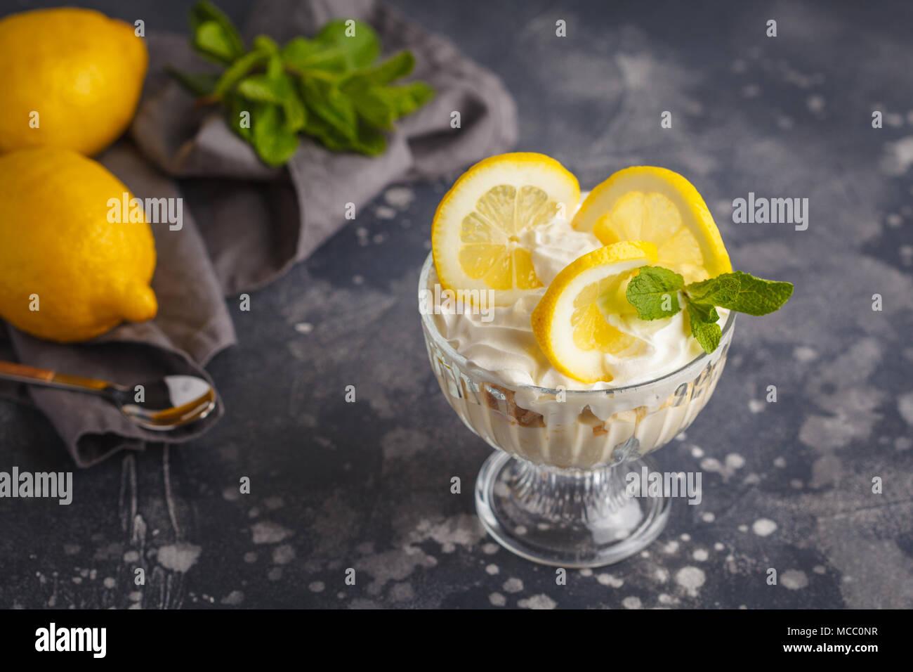 Limone dessert, limone inezia, cheesecake, panna montata, parfait. Mousse di frutta in vetro su uno sfondo scuro. Foto Stock