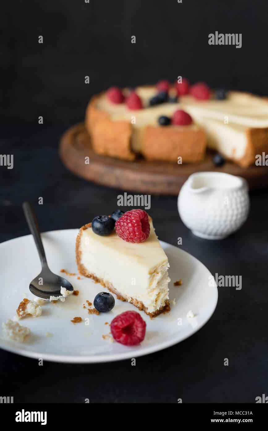 Fetta di cheesecake con morso mancante sulla piastra bianca. messa a fuoco selettiva Immagini Stock