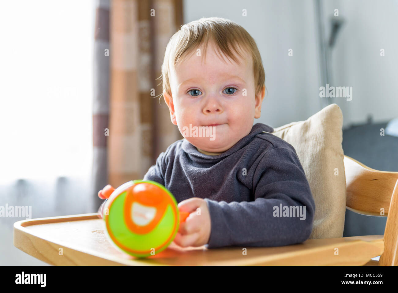Piscina ritratto di baby acqua potabile da orange bicchiere bicchiere. Immagini Stock