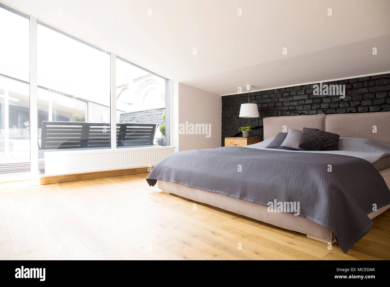 Biancheria da letto grigio sul letto in camera da letto luminoso ...