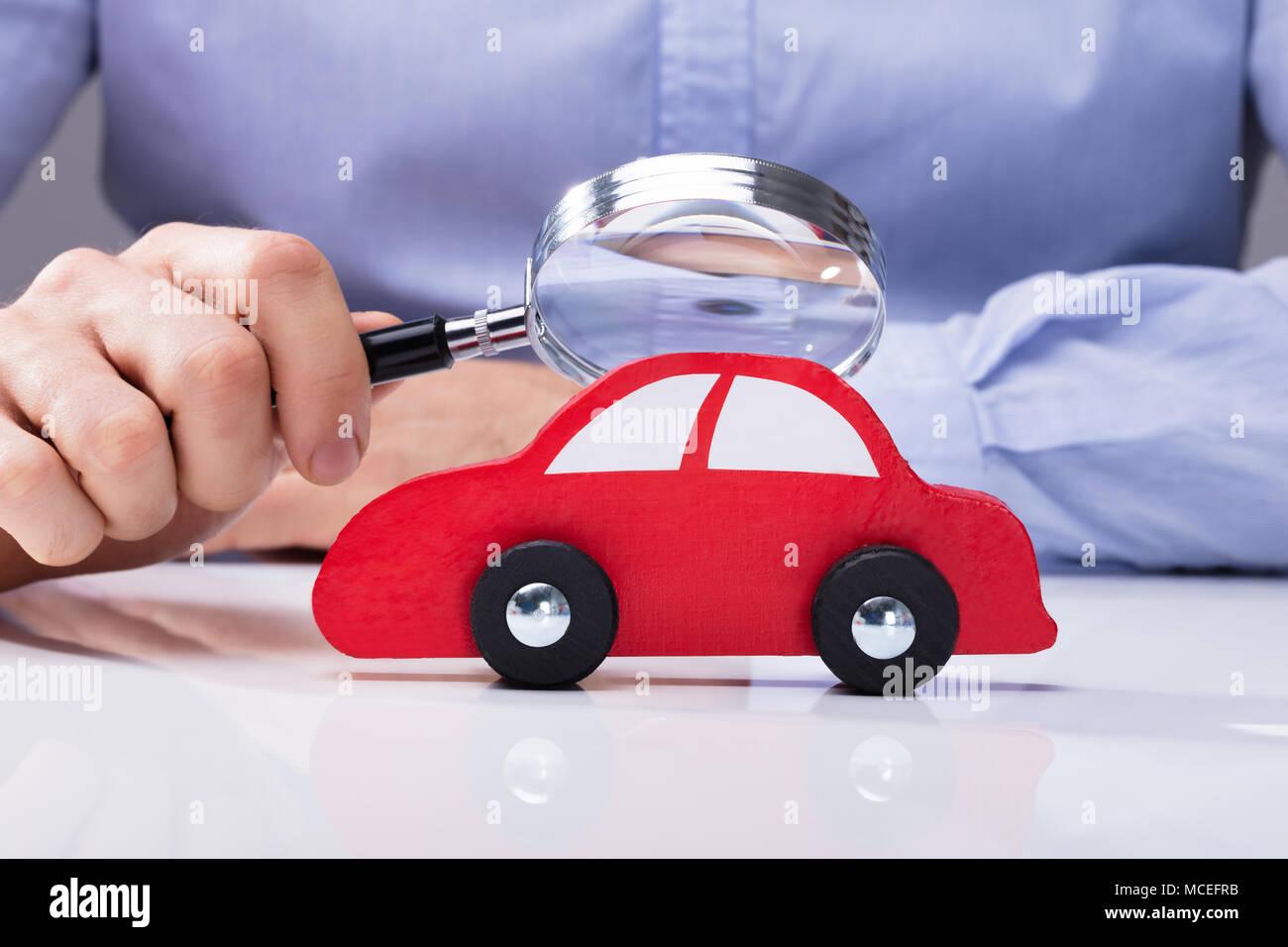 Close-up di mano di una persona in cerca di auto rossa attraverso la lente di ingrandimento Immagini Stock