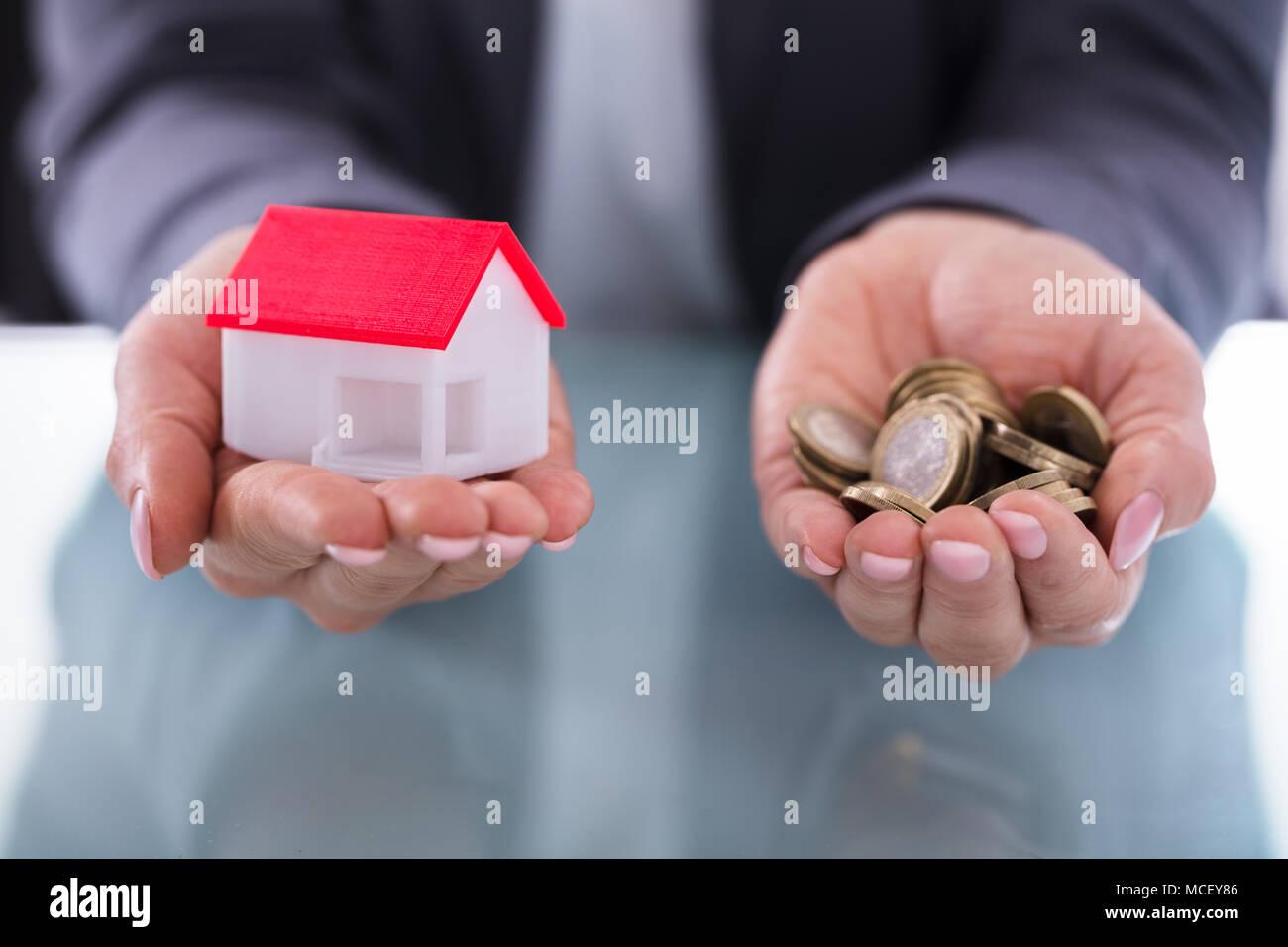 Close-up di un imprenditore la mano che trattiene le monete e modello di casa Immagini Stock