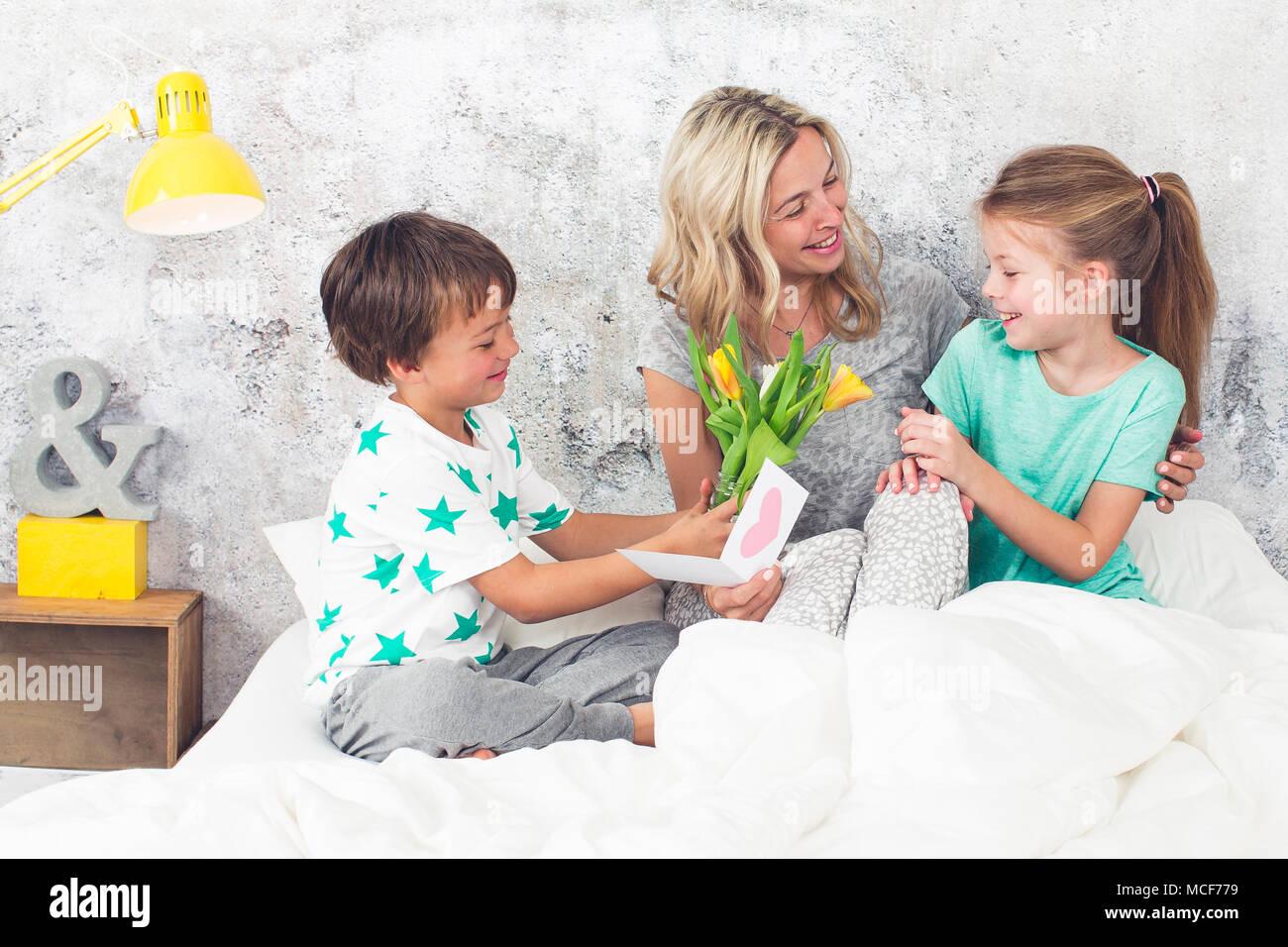 La famiglia felice - i bambini a congratularmi per la Festa della mamma Immagini Stock