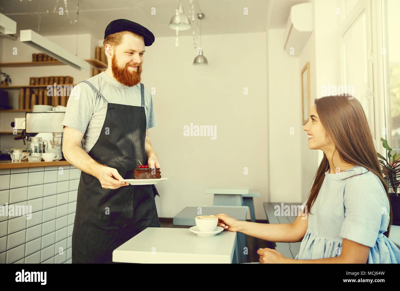 Caffè il concetto di Business - cameriere o barista dando una torta al cioccolato e parlare con caucasian bella signora in vestito blu presso la caffetteria. Immagini Stock