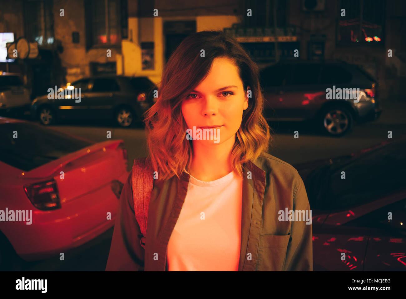 8bb7f46e6b63 Ritratto di attraente giovane donna indossa abbigliamento casual di notte  nel rosso luce al neon. Hipster ragazza è in piedi su una strada di città  ...