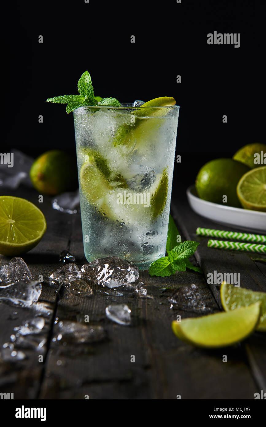 Cocktail Mojito con lime e menta in highball bicchiere con ghiaccio su di un legno scuro dello sfondo con copia spazio. Immagini Stock