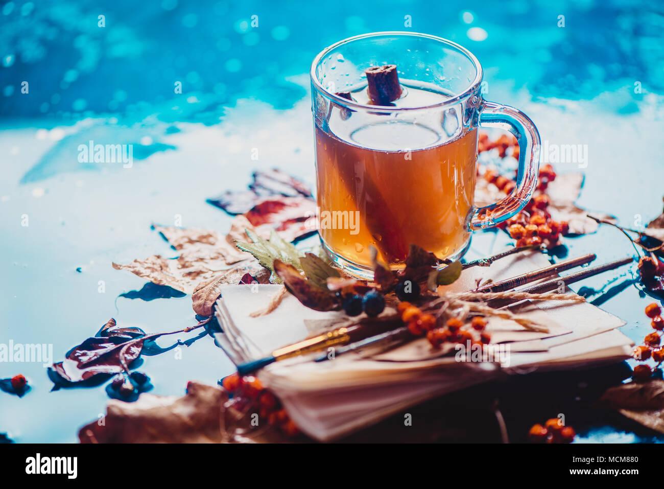Pioggia ancora la vita con un vetro tazza da tè sul bagnato sullo sfondo di legno con copia spazio. Concetto di autunno con caduta foglie e una pila di artista scetches wit Immagini Stock