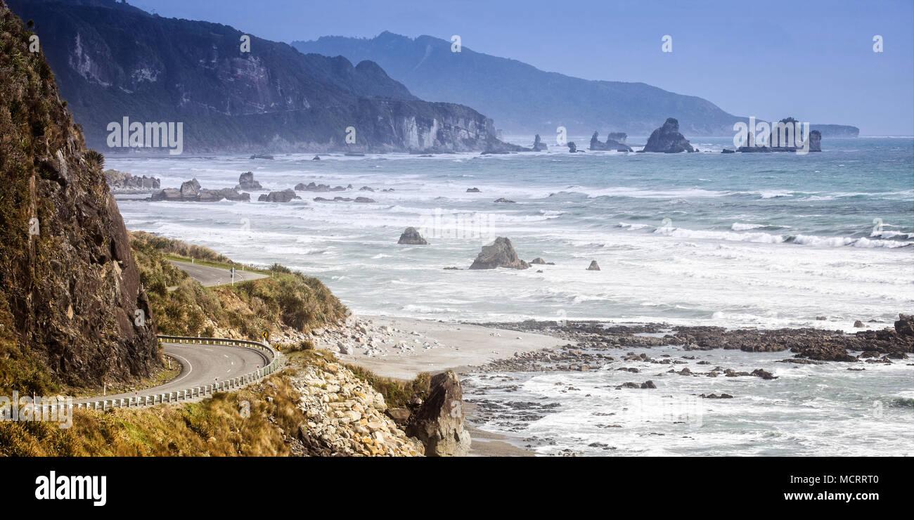 L'avvolgimento lato oceano strada lungo la costa Occidentale Regione del South Island, in Nuova Zelanda. Immagini Stock