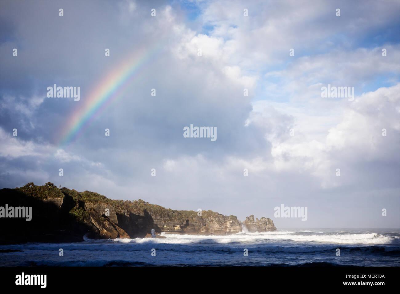 Un arcobaleno mostra su Dolomite Punto di Punakaiki lungo la costa Occidentale Regione del South Island, in Nuova Zelanda. Immagini Stock