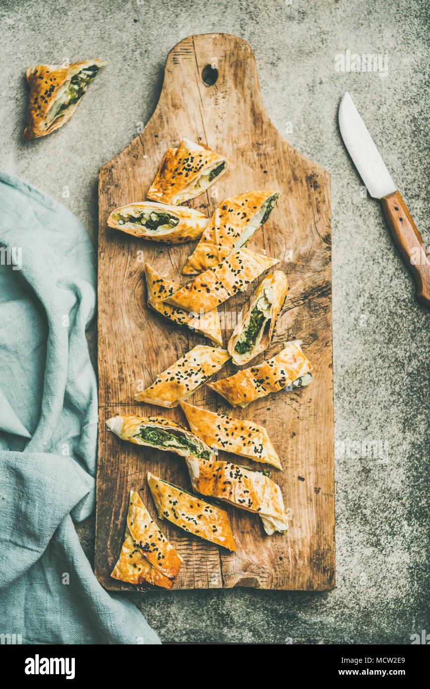 Flat-lay di fresco borek turco rotolo con spinaci, formaggio feta, nero semi di cumino tagliare in fette su tavola di legno su sfondo concreto, vista dall'alto. Tr Immagini Stock