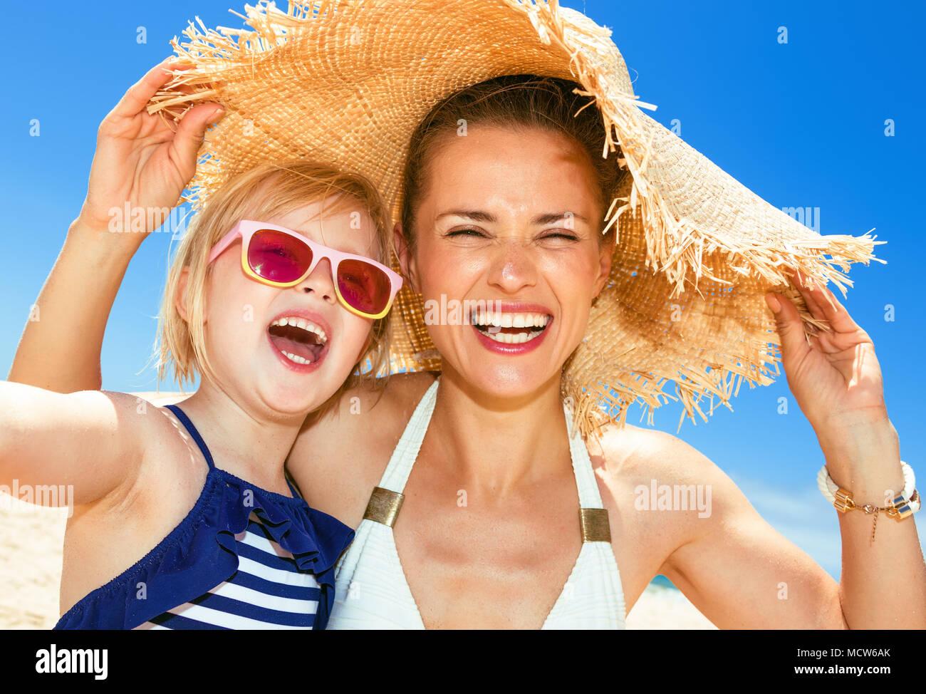 E per il divertimento di tutta la famiglia sulla sabbia bianca. Felice moderno la madre e il bambino in costume da bagno sul Seacoast tenendo selfie Immagini Stock