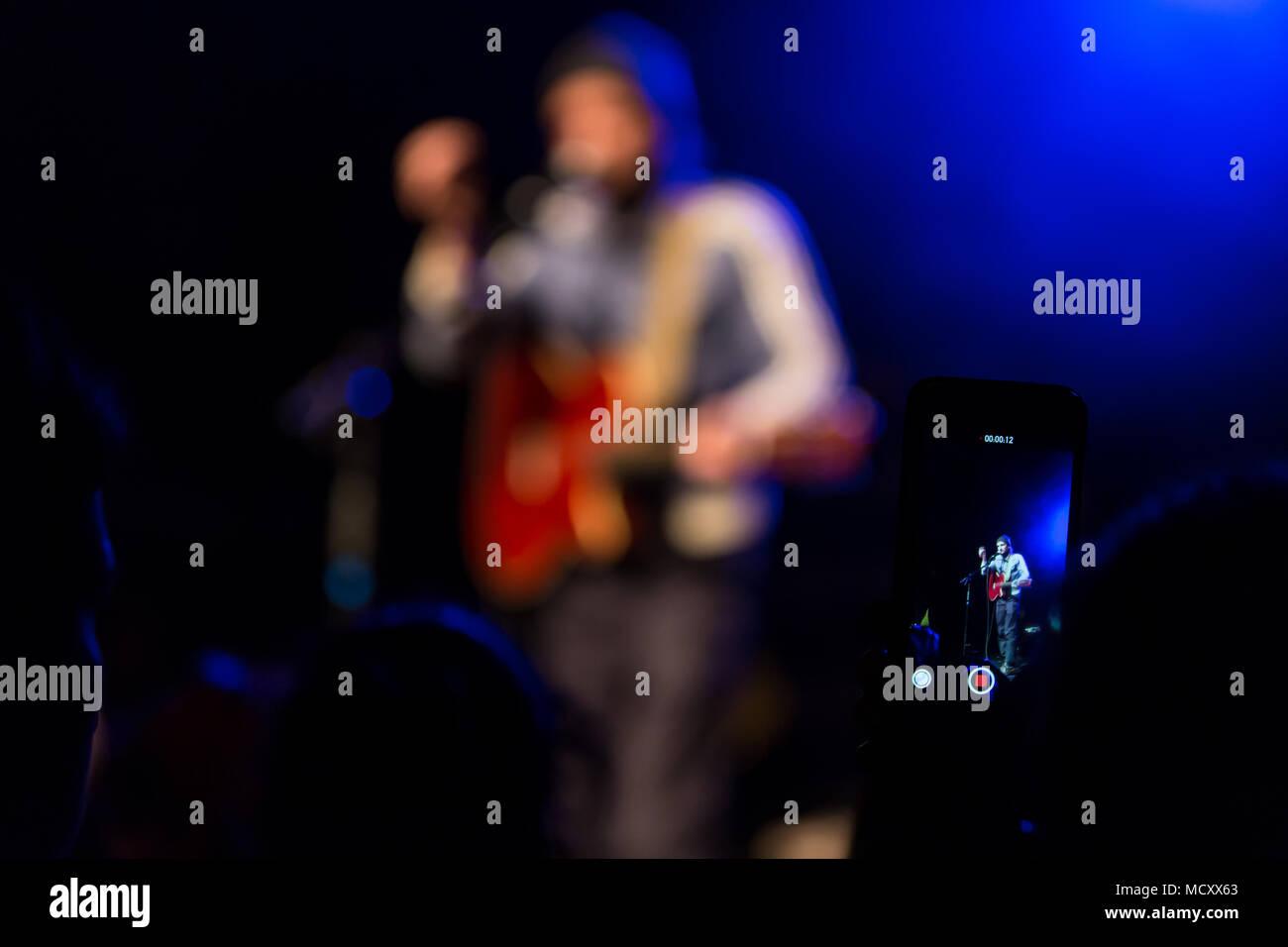 Concertgoer prende una foto con i-Phone al concerto del Swiss cantante e cantautore Shem Thomas live presso il Schüür Immagini Stock