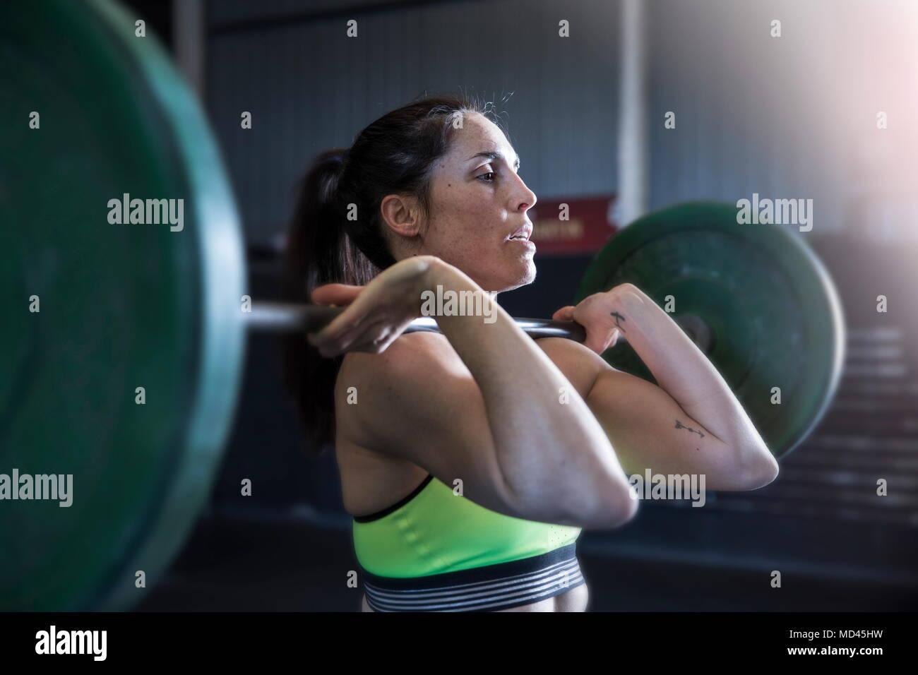 Donna esercizio in palestra, utilizzando barbell Immagini Stock