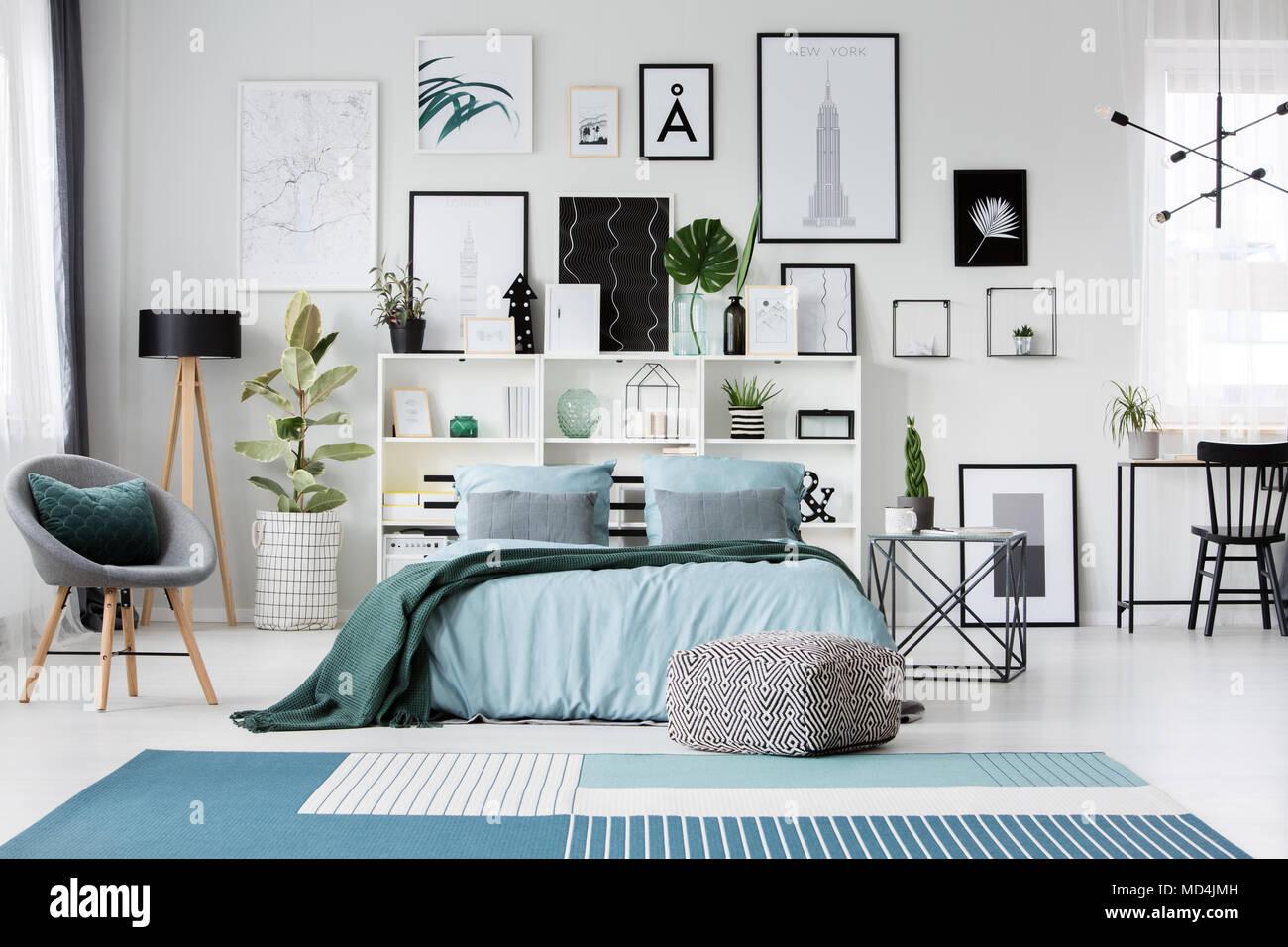 Tappeti blu e pouf vicino al letto in camera da letto spaziosa con ...